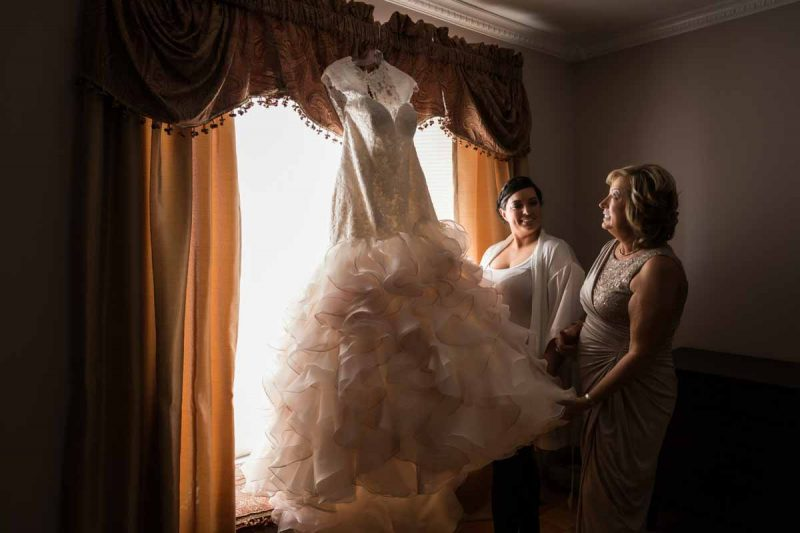 Bride and Mom holding the wedding dress