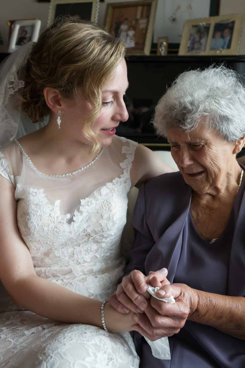 Bride and grandmother holding hands