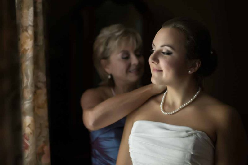 Mom attaching bride's necklace