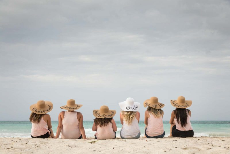 Bridesmaids wearing hats on beach