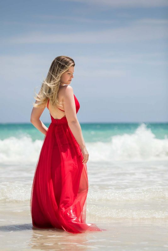 Bride with red dress on the beach