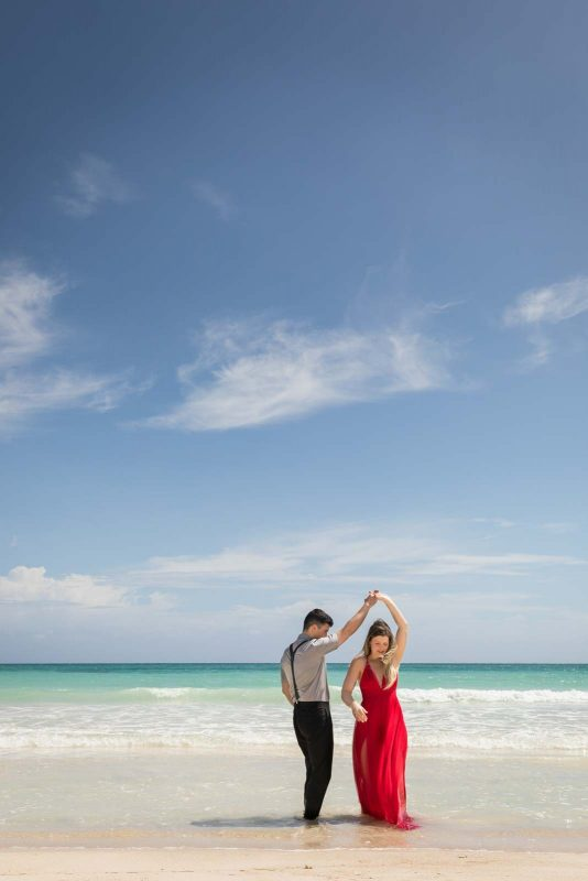 Newlyweds twirling on beach