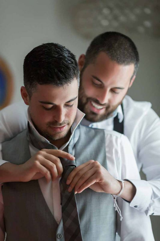 Best man helping groom with tie