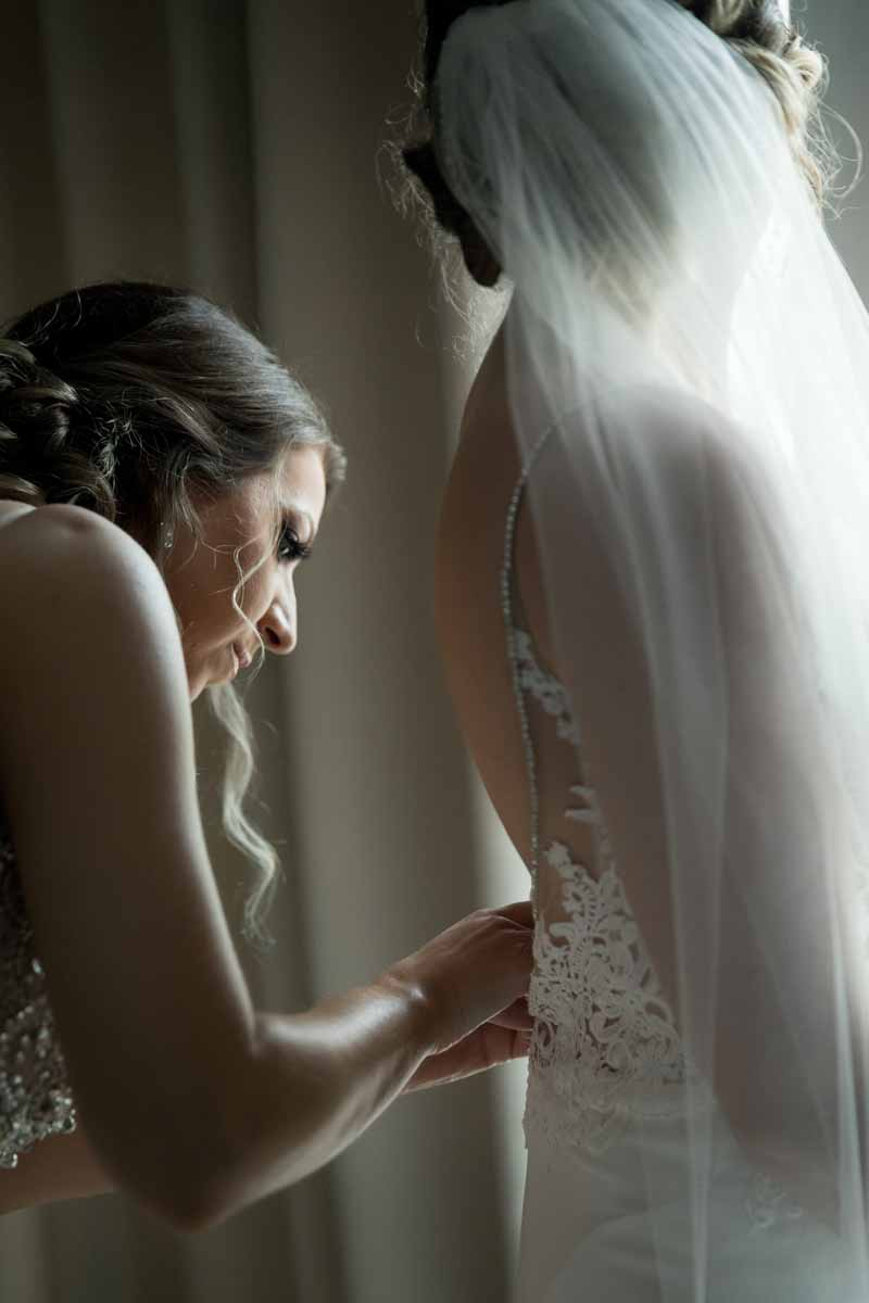 Buttoning the back of bride's dress