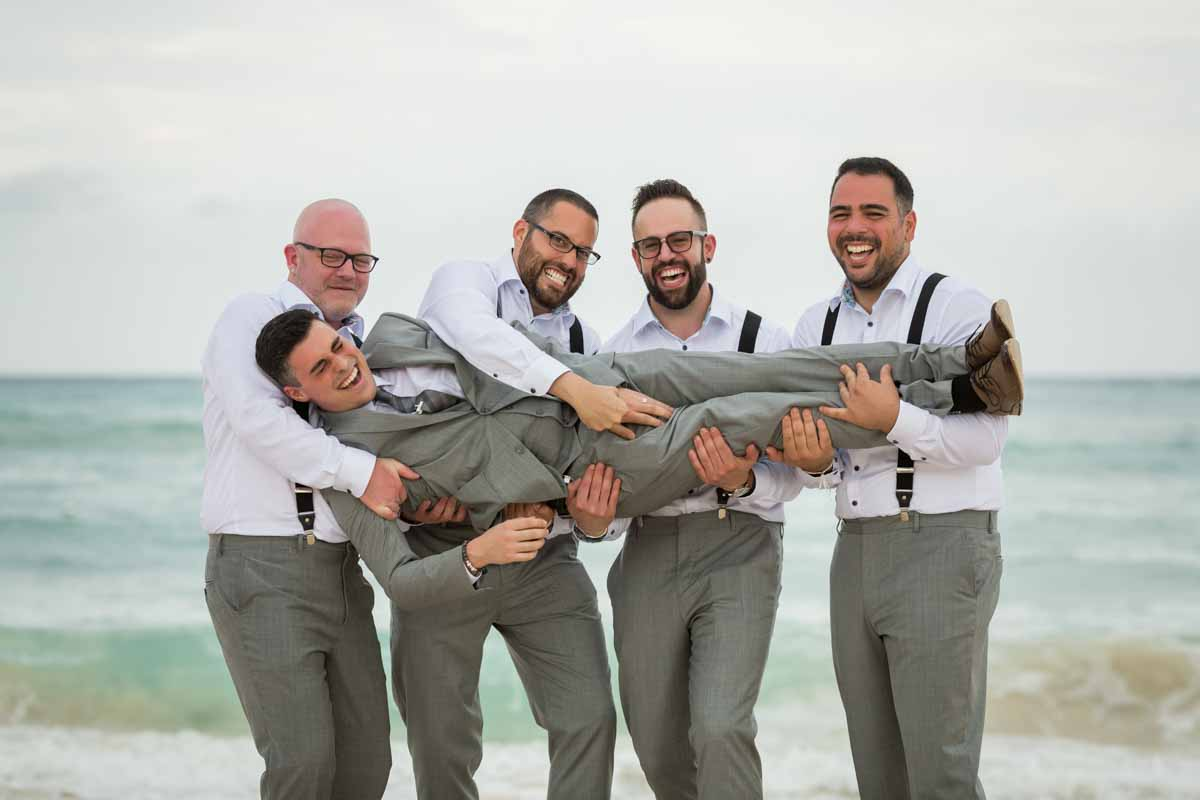 Groomsmen lifting up groom