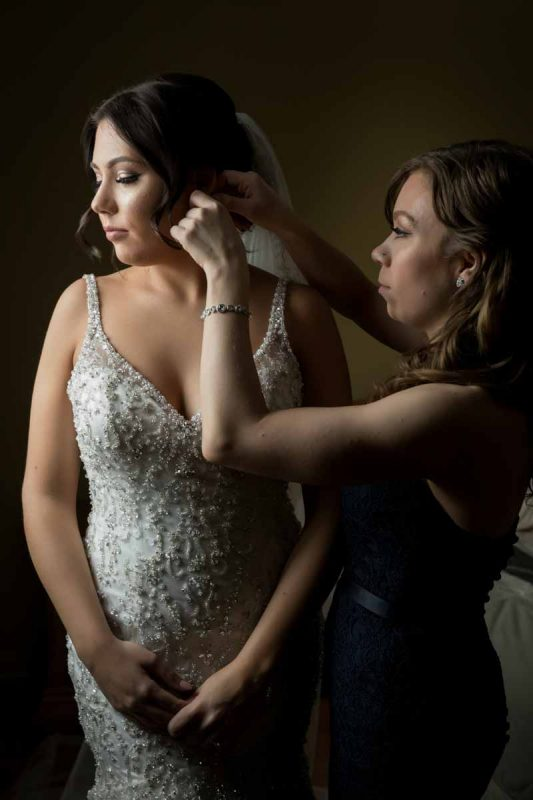 Putting on bride's earrings