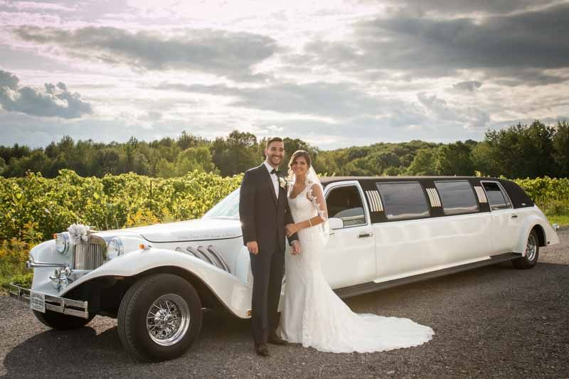 Newlyweds in front of limousine